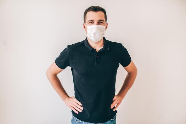壁を越えて分離された若い病人。黒いシャツの男は医療用保護マスクを着用します。健康とウェルネスに注意してください。カメラでポーズ。