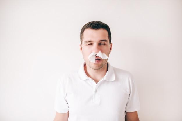 白い壁に分離された病気の若者。男は鼻にティッシュを抱えて一人で立ちます。病気の人は息を吸ったり吐いたりできません。問題を吸い込みます。はなたれ。