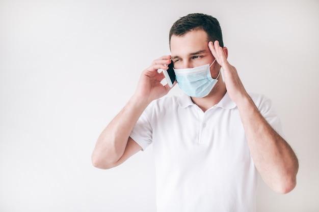 白い壁に分離された病気の若者。男は顔の医療用保護マスクを着用します。スマートフォンを使用して医師との診察のために医師を呼び出す。
