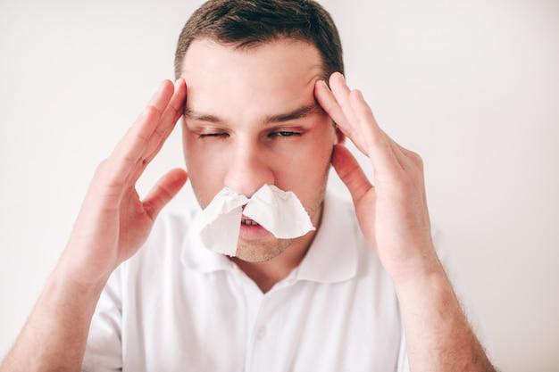 白い壁に分離された病気の若者。頭痛に手を繋いでいる鼻の組織を持つ男の肖像画。男は痛みと鼻水に苦しんでいます。画像の病気の人。