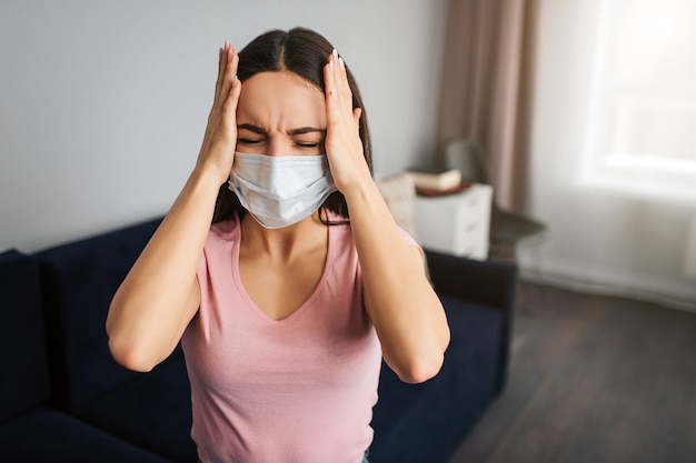 Young sick woman hold palms of her hands on head. she keep eyes closed. model has terrible headache. she suffer. young woman sit in room alone. her mouth covered with mask.