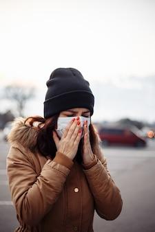 의료 보호 마스크에 젊은 아픈 여자는 거리에 기침. 소녀가 기침에 감염되었습니다. 보균자, covid-19, 코로나 바이러스, 증상. 유행성 코로나 바이러스. 독감에 걸린 사람. 재채기의 클로즈업.
