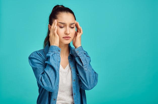若い病気の女性の肖像画、青い壁、否定的な感情。表情、スタジオでカメラを見ている女性、感情的な概念、感情