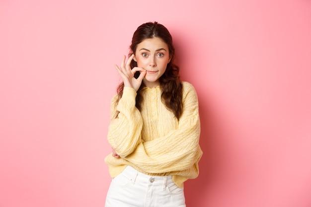 Молодая глупая девушка сплетничает, обещает хранить в секрете, застегивает рот на печать, закрывает губы, делая табуированный жест, стоит у розовой стены