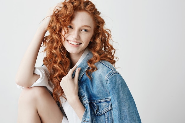 Young sincere girl with red curly hair smiling looking in side . copy space.