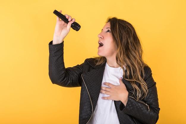 노란색에 마이크와 함께 노래하는 검은 가죽 재킷을 입고 젊은 가수 소녀.