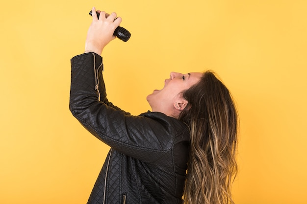 Young singer girl wearing black leather jacket singing with microphone on yellow.