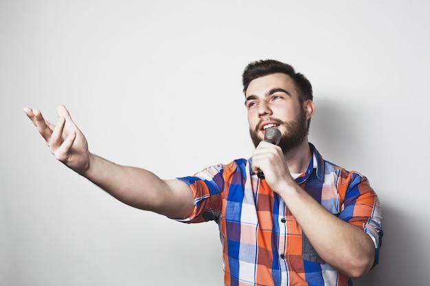 灰色の背景にマイクを持つ若い歌手の男