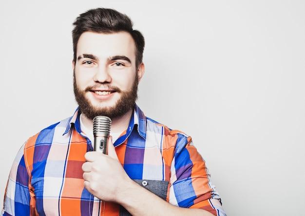 회색 배경 위에 마이크가 있는 젊은 가수 남자