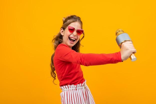 Молодая певица с микрофоном в руках на желтом