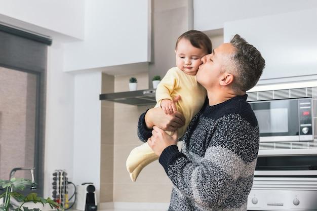 팔에 그를 잡고 그의 작은 아기를 키스하는 젊은 싱글 아버지
