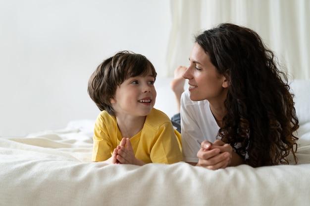 Молодая мать-одиночка любит проводить утро, лежа на кровати с сыном дошкольного возраста, разговаривая и общаясь