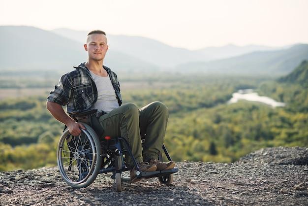 山で自然の美しさを楽しんでいる車椅子の若いsirious男。障害を持つ人々