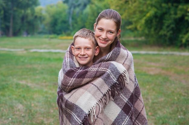 公園で格子縞に覆われた妹と弟のスタンド