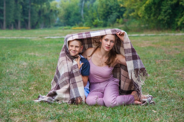 そばかすのある妹と弟が公園で格子縞に覆われて立って、暖かく、笑顔でカメラを見ています。