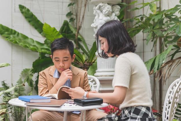 Молодая сестра учит домашнее задание младшему брату внимание слушать