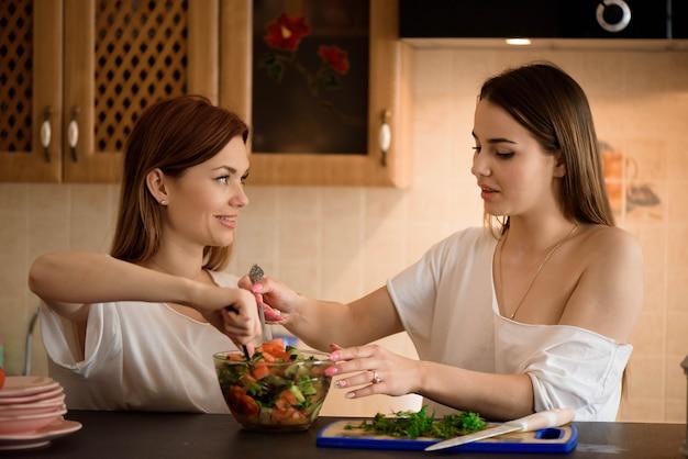 집에서 야채 샐러드를 만드는 젊은 자매.