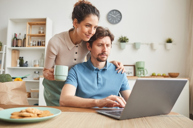Молодой сидит за столом на кухне и работает за ноутбуком, а его девушка стоит рядом и пьет кофе