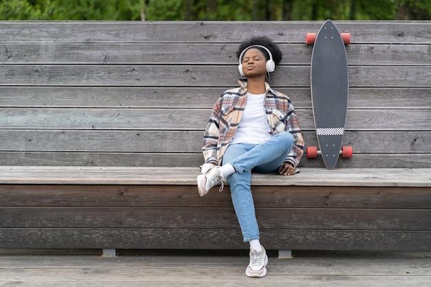 젊은 스케이트보더 소녀는 롱보드 근처 도시 공원 벤치에서 눈을 감고 음악을 듣습니다.