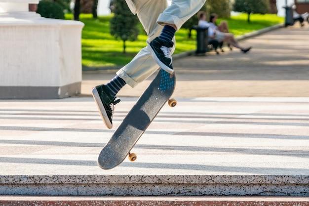 Юный скейтбордист в парке батуми, спортивная жизнь. люди
