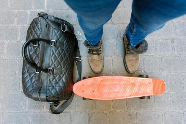 彼のスケートの上に立っているブーツとジーンズの若いスケートボーダー。