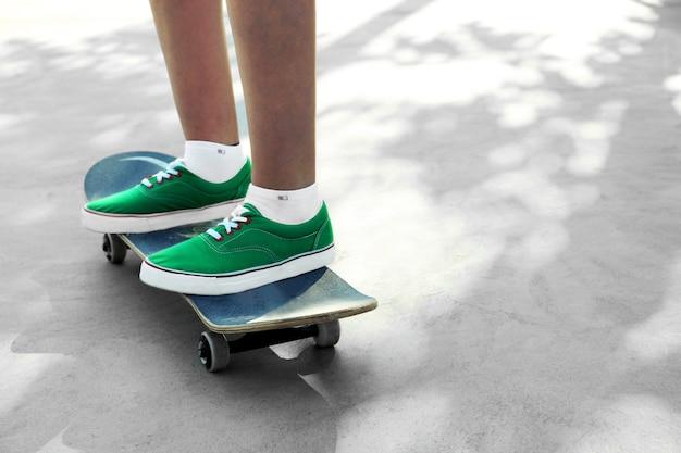 스케이트에 서있는 덧 신에 젊은 스케이트 보더