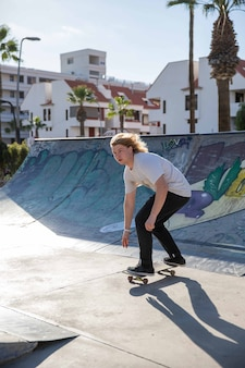 A young skateboarder is having fun at the skatepark on the ramps in summer