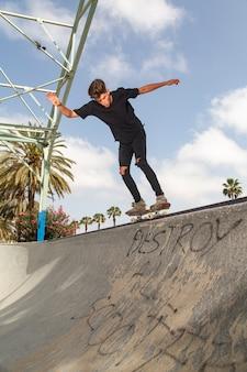 Молодой скейтбордист, выполняя трюки в парке.