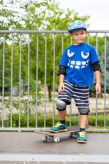 スケートパークのスロープの頂上に立って、スケートボードに足を乗せてカメラに向かって微笑んでいる若いスケートボーダー
