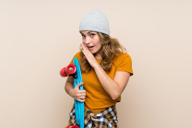 Young skater blonde girl over isolated wall whispering something
