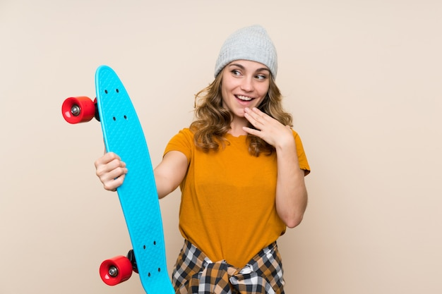 Young skater blonde girl over isolated wall with surprise and shocked facial expression