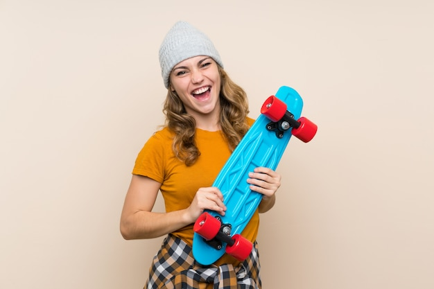 Young skater blonde girl over isolated wall