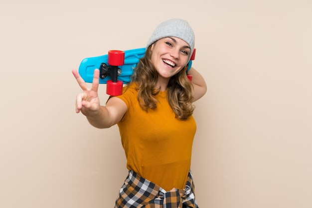 Young skater blonde girl making victory gesture over isolated wall