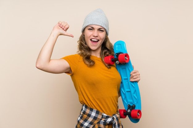Young skater blonde girl proud of herself over isolated wall