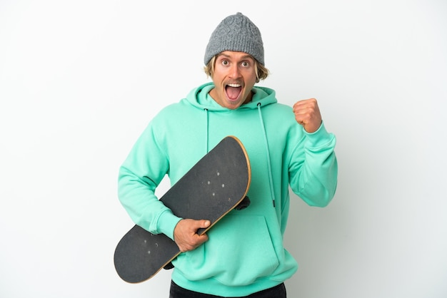 Young skater blonde man isolated celebrating a victory in winner position