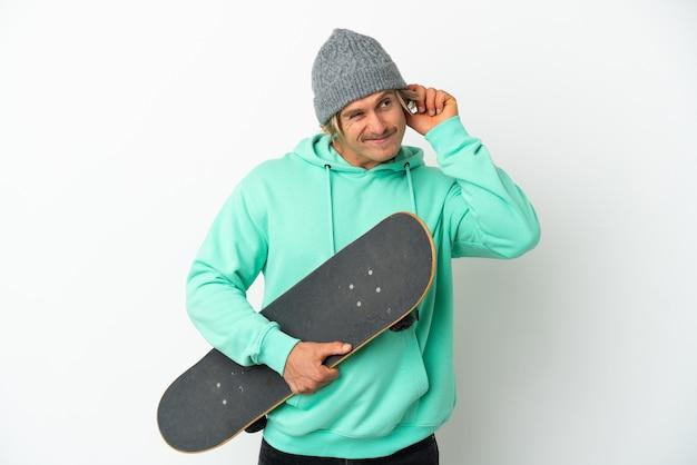 欲求不満と耳を覆っている白い背景で隔離の若いスケーターブロンドの男