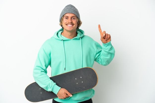 Young skater blonde man isolated pointing up a great idea