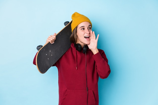 Young skater caucasian woman isolated shouting and holding palm near opened mouth.