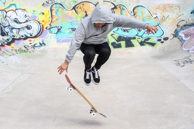 スケートパークでジャンプトリックを行う若いスケーター。