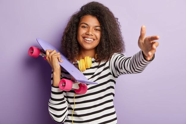 Femmina giovane pattinatore in posa con bordo lungo