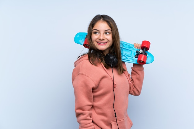 Young skater girl over isolated wall
