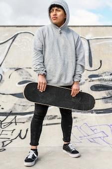 若いスケーターがスケートパークでスケートボードでポーズします。