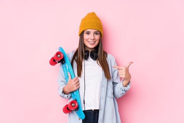 シャツのコピースペースを手で指しているスケートの人を保持している若いスケーターの女性、誇りと自信を持って