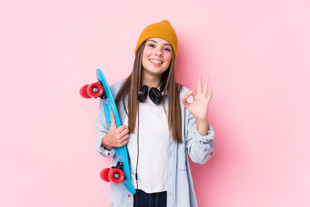 Young skater woman holding a skate cheerful and confident showing ok gesture.