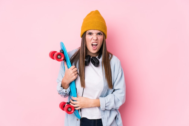 Young skater woman holding a skate screaming very angry and aggressive.