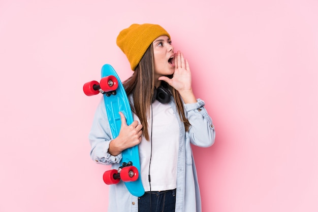 Young skater woman holding a skate shouting and holding palm near opened mouth.