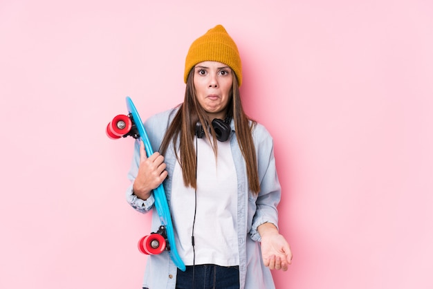 Young skater woman holding a skate shrugs shoulders and open eyes confused.