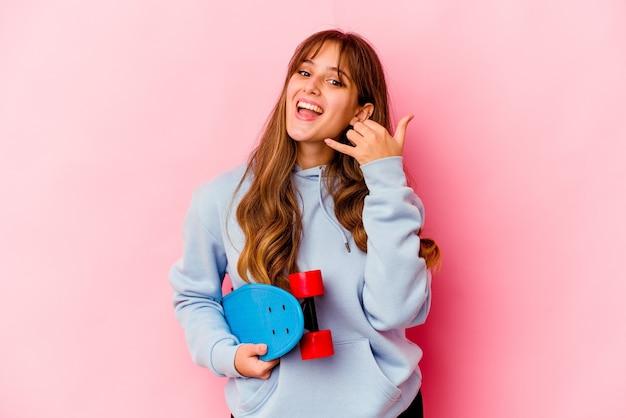 指で携帯電話の呼び出しジェスチャーを示すピンクの壁に分離された若いスケーターの女性。