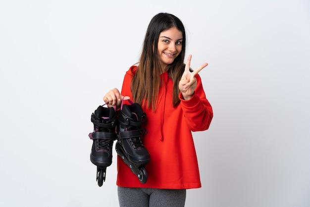 웃 고 승리 기호를 보여주는 흰색 배경에 고립 된 젊은 스케이팅 여자