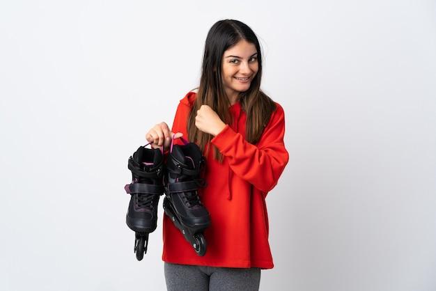 勝利を祝う白い壁に孤立した若いスケーターの女性